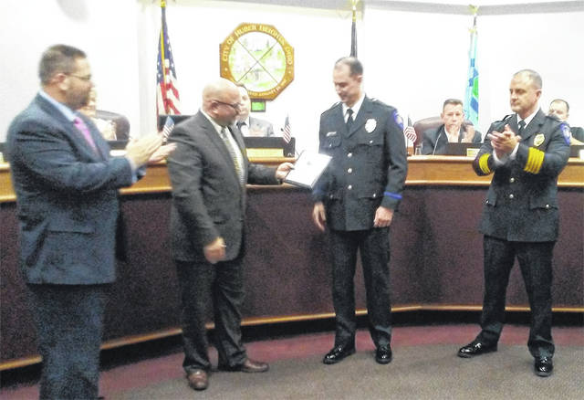 City Manager Rob Schommer presents police officer Scott Short with employee of the third quarter award while Mayor Jeff Gore and Police Chief Mark Lightner look on.