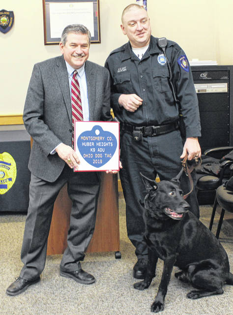 Montgomery County Auditor Karl Keith (left) presents a dog license to Huber Heights K-9 Adu and his handler Officer Mike Reckner.