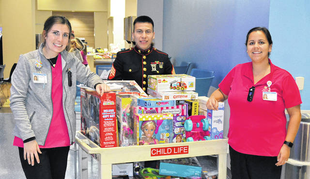 Sgt Miguel Contreras assists Children's Medical Center Child Life Staff delivering toys to inpatient children.