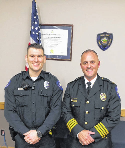 Huber Heights Police Chief Mark Lightner (right) stands with one of the city's new police officers, Chris Elliott, whom he introduced at Monday's city council meeting.