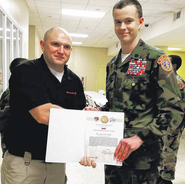Unit Commander Keagan Miller presents 3rd Degree Life Saving Award to Young Marine Gunnery Sergeant John Sollinger