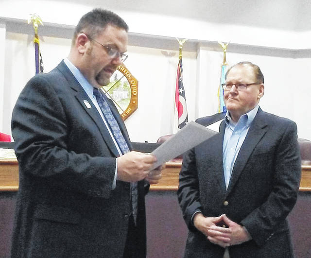 Mayor Jeff Gore reads a proclamation declaring March as Red Cross Month in Hubert Heights while Cory Paul, executive director of the American Red Cross Dayton Chapter, looks on during Monday's City Council meeting.
