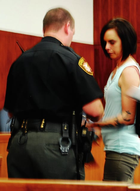 Heather D. Gaus is taken into custody following a sentencing hearing Tuesday. Gaus previously pleaded guilty to theft for deceiving community residents into thinking she had cancer and receiving money from the hoax.