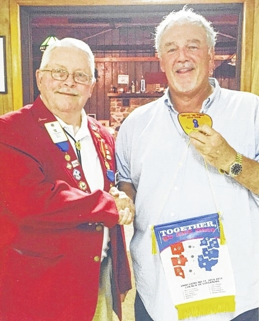 Woodstock Lions Club President Tim Kemper, right, receives the Distinguished Service Award at the Woodstock Lions Club's July 7 meeting. Last year's district governor, Karl Cox, left, presents the award. The Woodstock Lions Club is the top club for new members in the district.