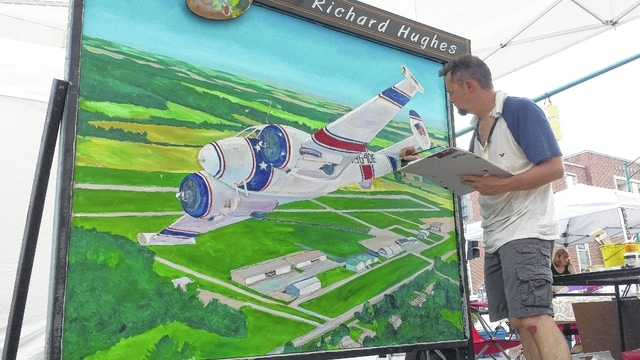 Urbana artist Richard Hughes works on his painting of the Grimes Flying Lab. Attendees at MERFI on Saturday can watch Hughes work on the painting. Once completed, Hughes will sell the painting.