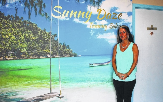 Sheryl Cain, owner of Sunny Daze Tanning Salon at 1637 E. U.S. Route 36, Suite 2, is pictured in front of a beach mural painted inside the salon during renovations earlier this year.