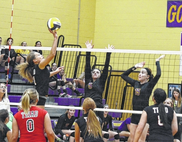 Triad's Madison Dolby (left) spikes a ball into Mechanicsburg's playing area while Katie Bush (5) and Emma Dunham (15) try for a block.