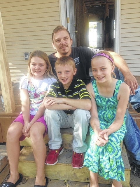 William Baber and his three children will soon move into their new home at 360 Windsor Ave. in Urbana. Pictured on the steps of the home, built by Habitat for Humanity of Champaign County Ohio, are Baber and his children, from left, Lily, William Jr. and Jerzie.