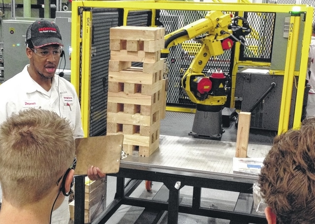 HTM associate Donovan Williams discusses a Jenga-playing robot with Ohio Hi-Point Career Center students touring the plant, kicking off National Manufacturing Day activities planned by Honda. Williams and other associates along the tour stressed the need for skilled workers who can program and repair the multitude of high-tech machines throughout the plant. Students from a score of other area high schools were scheduled to tour the plant over the next several business days.