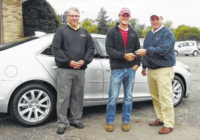 Austin Woodruff of Urbana, center, is pictured taking possession of his new car from Trenor Motors President Roger Tehan, right, while salesman Tony Warye looks on. Woodruff received $30,000 toward the purchase of a new car for getting a hole-in-one at the Bill Butler Champaign Open in August.