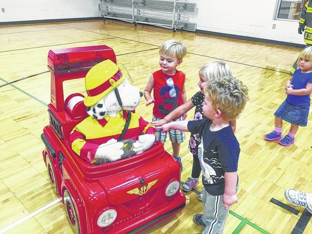 Sparky the Fire Dog visited the Champaign Family YMCA on Wednesday and had a fine time with daycare and preschool children, including, from left, Jeremiah Steinmetz, Claire Huffman and Braedy Fox. Sparky's friends at the Urbana Fire Division tagged along to teach the children fire safety skills.