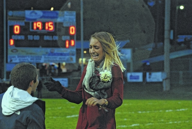 Urbana High School alumni football player Aaron Sidders (left) proposed to alumni cheerleader Jordan Ropp during pregame of Friday night's game against visiting Greenon. In photo, Ropp accepts the ring and cries after it was placed on her finger. Sidders and Ropp were high school sweethearts and have been dating for four years. The proposal in front of the home bleachers on the football field was a surprise.