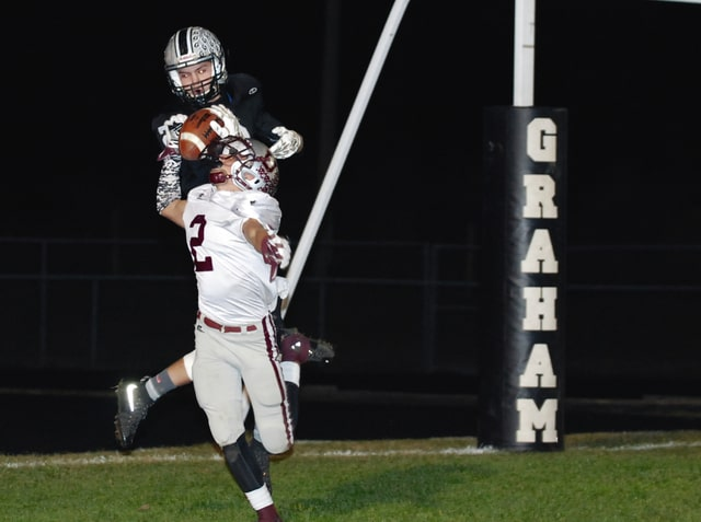 Graham's Tyler Powell catches a touchdown pass during the first half of Friday night's game as Urbana's Logan Rooney defends on the play.