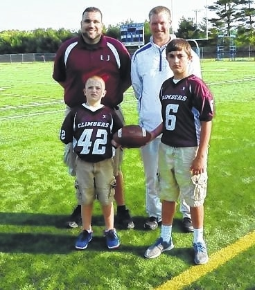 Urbana Little Climbers Football Coach Justin Cain poses with Shane Hoffman (#42) and Riley Wilson (#6) with Blue Knights Head Football Coach Tyler Haines.