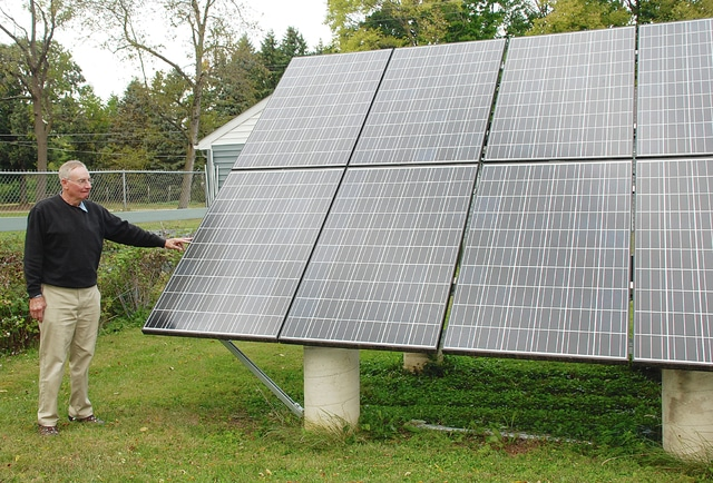 Urbana resident Ward Lutz stands with solar panels that help power his home. The property will be part of the Green Energy Ohio Tour slated for this weekend.