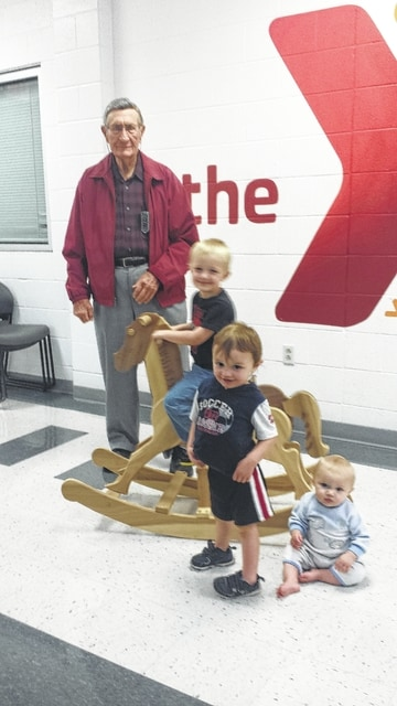 YMCA member Leroy Blazer, a long-time craftsman and supporter of the auction, displays his handmade and fully-functional rocking horse to Daniel, William and Brien, children of Y Daycare staffer Sarah Campbell. Blazer's hand-crafted wooden toys and replicas are popular at each year's auction.