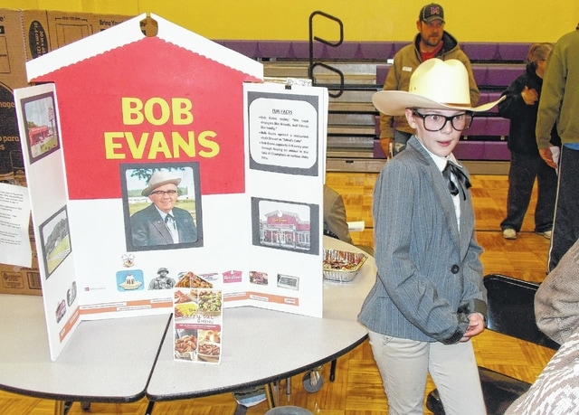 Fourth-grade students at Dohron Wilson Elementary School in Mechanicsburg took part in the fifth annual Famous Ohioan Wax Museum on Monday, which was attended by 150 individuals. Ella Forrest is pictured portraying Bob Evans. The students stood stationary like wax figures next to the informational displays about the individuals they were portraying.