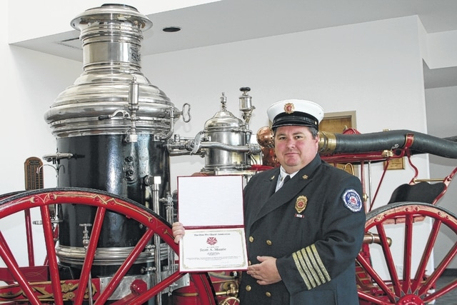 Displaying his designation, Chief Massie stands in front of the first fire engine in the village of St. Paris, an 1884 Ahrens-Fox Steamer.