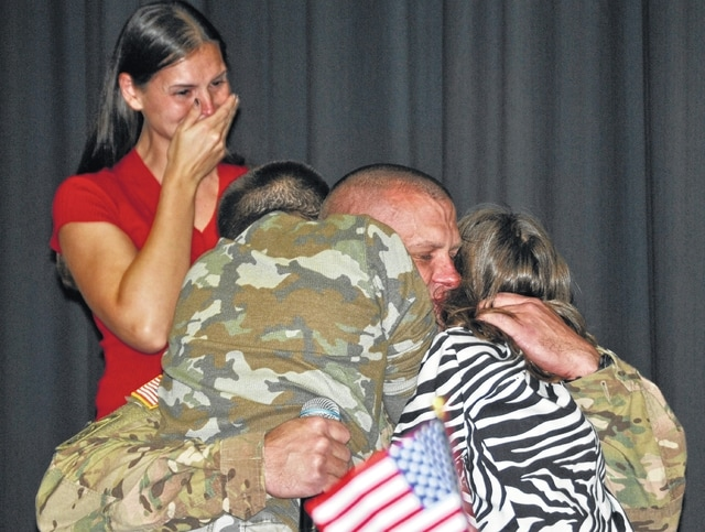 Sgt. Jason Conley gives his children Daniel and Bethany an extended hug while wife and mom Jennifer Conley looks on. Sgt. Conley had been deployed to Iraq since January, and had gone 10 months without seeing his kids before surprising them at Riverside Elementary on Veterans Day.