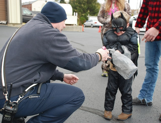 Urbana firefighter/paramedic Jonathan DeCola stoops down to treat 4-year-old Hunter Kerns to some candy during Beggars Night in Urbana Saturday night. Municipalities around Champaign County greeted the costumed children for Trick-or-Treat.