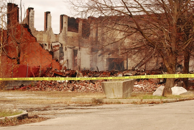 Police crime scene tape is shown at the rear of the burned out Q3/JMC abandoned industrial site on Monday afternoon.