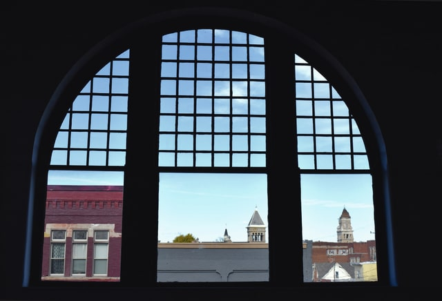 Pictured is a north-facing expansive window set in the upstairs of 117-119 Miami Street that houses the Champaign County Arts Council and Mike Major's Sculpture studio at street level.