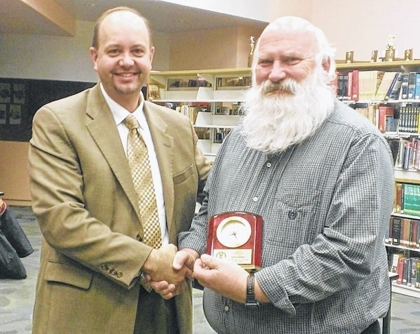 West Liberty-Salem Local Schools Superintendent Kraig Hissong, left, presents retiring board member Jim Hoffman with a memento in recognition of 20 years on the school board. Hoffman's last meeting was Dec. 15.