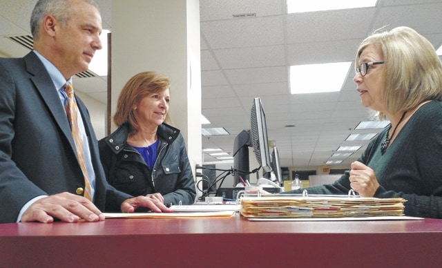 Former state representative Matt Huffman, left, along with his wife, Sheryl, file paperwork with Michele Foster of the Allen County Board of Elections to run for the 12th District Ohio Senate seat Thursday.