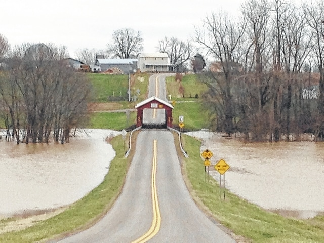 After inundating the area with rain earlier this year, Mother Nature bestowed on western Ohio another blast of spring-like weather, only she waited until December to do it. In the warmest December recorded for the region, several inches of rain over the past two weeks again flooded many parts of Logan County, closing roads and isolating rural farms. Shown here is the McColly covered bridge on county Road 13 in Logan County near the Shelby County line. Several other bridges north of the McColly bridge toward Indian Lake have been closed because of the flooding.