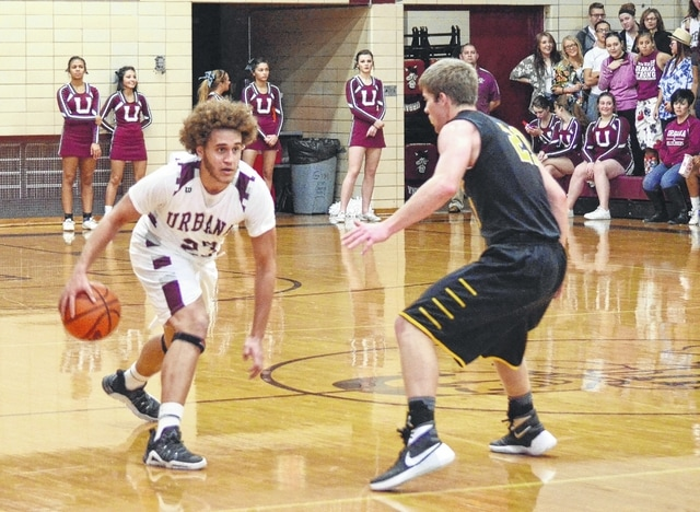 Urbana's Cameron Logwood (left) works to shake his defender Tuesday night at Urbana High School. Logwood finished with 23 points.