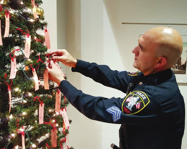 Urbana Police Sgt. Josh Jacobs hangs a tag on The Giving Christmas Tree Thursday. Located in the lobby of the Urbana municipal building, 205 S. Main St., residents who remove a tag from the tree are asked to purchase a Christmas present for a local child in need.