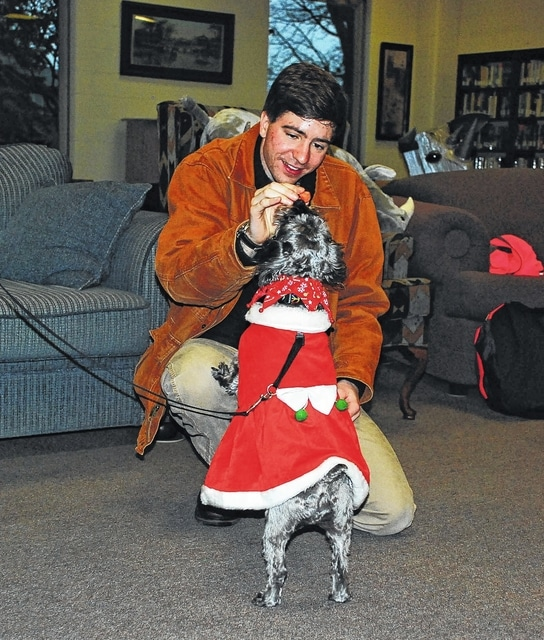Urbana University second-year graduate student Kevin Fidler, of St. Paris, took a break from studying for fall semester finals on Tuesday to spend time in the Swedenborg Memorial Library with Tickles, a female schnauzer/terrier mix. Fidler, who is pictured feeding treats to Tickles, has attended the pet therapy sessions every year since Tickles' owner, Nancy Sleeper, held the first one at UU back in April 2013. Fidler, who is pursuing a MBA degree, was valedictorian of the class of 2014 at UU.