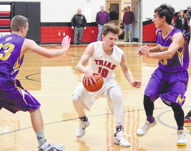 Triad's Colby Watson dribbles between Mechanicsburg's Jack Butcher (left) and Mack Cushman (right) during Tuesday's contest at Triad High School.