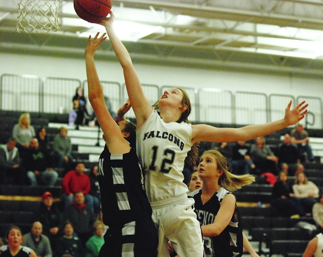 Graham's Bethany Horner (12) goes up for a basket against a pair of Greenon defenders during Wednesday night's game at Graham. The Falcons won the game, 37-32, in CBC/MRD action.