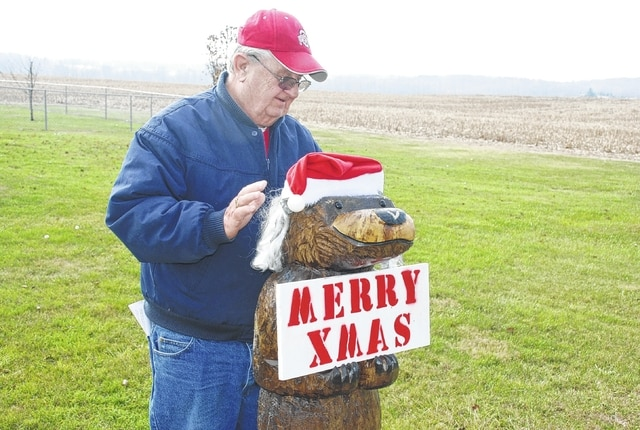 Richard Randall of the Westville area places a Christmas hat on the hand-carved wooden bear crafted from the trunk of an old tree in his front yard on Monday. Randall lives at 4563 W. U.S. Route 36. Temperatures are expected to stay above normal this week and into this weekend, allowing locals to do outdoor Christmas decorating in comfort.