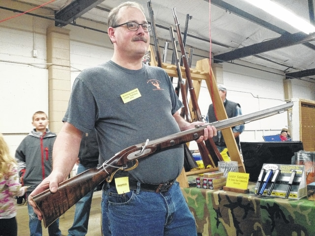 Craig Kelly | The Lima News Lester Salisbury, owner of S&S Muzzleloading Shop in Rockford, holds a 50-caliber custom-built muzzleloading rifle Saturday at the Tri-State Gun Show at the Allen County Fairgrounds.