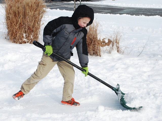 Logan Decker, who turns 7 years old today, shovels the sidewalks of his family's business, Abundant Life Chiropractic, in Urbana on Tuesday. Approximately two inches of snow fell by noon on Tuesday on top of an earlier layer of snow. Schools were closed and games were postponed as the winds picked up and made roads treacherous. Decker and his siblings made the most of the southern afternoon sunshine near Miami Street.