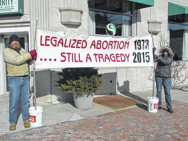 Local members of Champaign County Right to Life assembled Jan. 24 on Monument Square to mark the anniversary of 1973 U.S. Supreme Court ruling in Roe v. Wade. The annual event is a peaceful witness to the many lives lost to abortion in Champaign County (34 in 2014) and in the state of Ohio (21,186 in 2014). Pictured holding banner are Karl Ward (left) and Kay Miller.