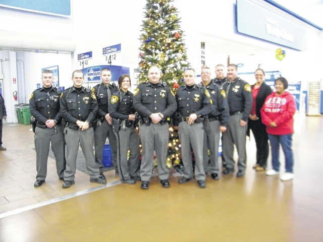 Pictured from left with tree are Deputy Brandon Fenwick, Deputy Bryan Dixon, Deputy Josh Welty, Deputy Melany Ward, Deputy Dennis Lyons, Sergeant Jason Byers, Captain David Rapp, Sheriff Matthew R. Melvin, Deputy Erich Hopkins, Christine Ryman, Evelyn Lucas.