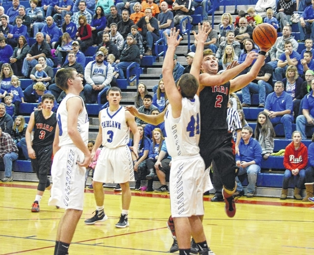 Triad's Ryan Boyd (right) slices through the defense and finishes at the rim Wednesday against Fairlawn at Piqua High School.