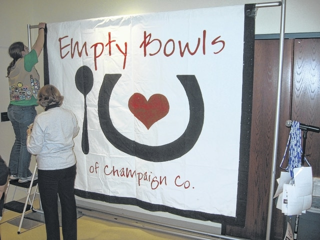 Pictured are volunteers hanging up a sign during a previous Empty Bowls of Champaign County event held at Urbana University.