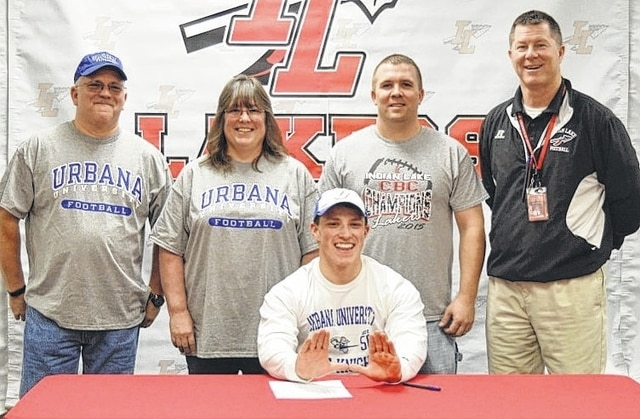 Joe Davidson, Deb Davidson, Coach Jonn Rapp and Coach Dave Coburn stand with Joey Davidson while he signs with Urbana University.