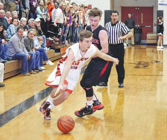 West Liberty-Salem's Luke Woods spins away from Triad's Colby Watson along the sideline Tuesday at WL-S. The Tigers forced overtime at the buzzer and pulled away to win.