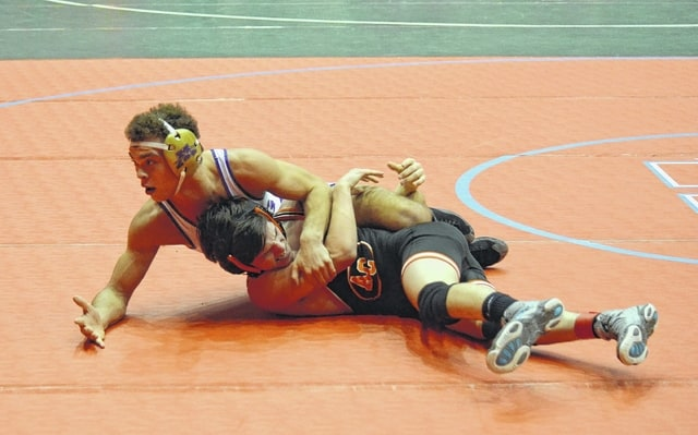 Mechanicsburg's Nick Miller pauses to check his criteria with the referee during the team duals quarterfinals in Columbus last weekend. This weekend, focus shifts to the individuals' competition with the sectional tournaments.
