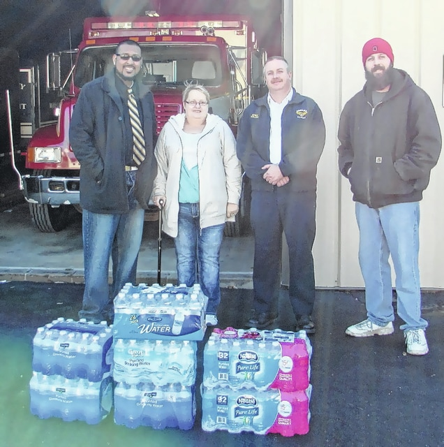Urbana Ohio Helping Hands organizers Andre Vactor, Kathy Mays and Trent Spriggs show off the collection of water that has just begun for Flint, Mich. The collection is being stored at the Urbana Police/Fire Division offices. Pictured are Vactor, Mays, Urbana Fire Chief Mark Keller and Spriggs.