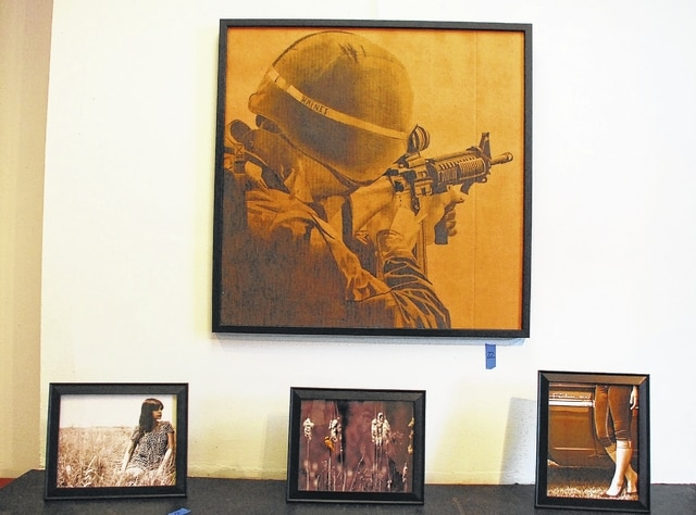 Pictured is a drawing on cardboard of a U.S. soldier along with three photographs. All four pieces are the works of Urbana University student Bri Haines and will be on display in the Miller Center for Visuals Arts from Feb. 17 through March 5 as part of the UU Faculty and Staff Art Show.