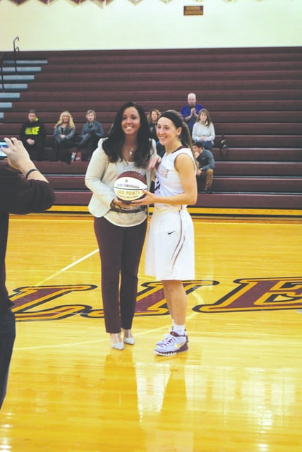 Triad graduate Kelsey Funderburgh of Walsh University, pictured with her coach, Maria Marchesano, was presented with a commemorative ball for scoring her 1,000th collegiate career point before a Walsh game on Jan. 16.