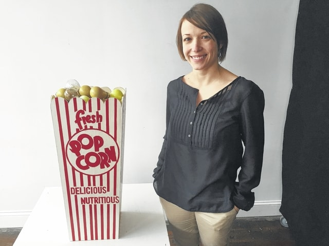 "Lydia Hess is the Administrative Manager of the GrandWorks Foundation/Gloria Theatre. She is a member of the Arts Council's Board of Trustees. She has created a replica popcorn box comprised of old incandescent hand-painted light bulbs from the theatre's marquee. She would like to thank her father, Steve Hess, for creating her wooden popcorn box ""canvas."" Lydia is one of 15 ""good people"" producing ""bad art"" for the 2016 Champaign County Arts Council's annual fundraiser."