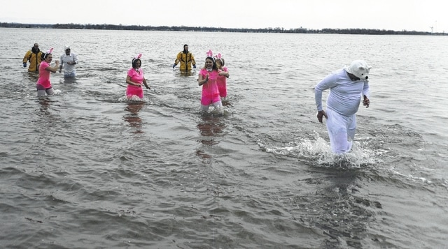 Swimmers in the Polar Plunge run back to shore after racing out to Indian Lake firefighters.
