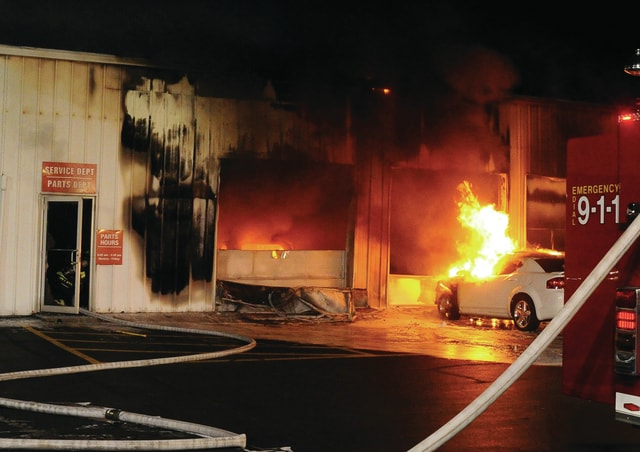 Mike Ullery | Daily Call Smoke and flames billow from the service department area and vehicles at the Paul Sherry dealership on North County Road 25-A on Wednesday night.